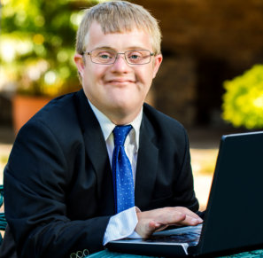 Close up portrait of young businessman with down syndrome using a laptop