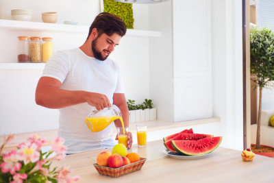 Portrait of man pouring fresh juice while standing in open space kitchen